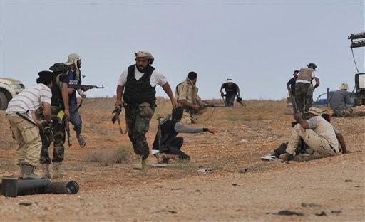 Rebeldes libios se preparan para cubrirse en un ataque contra Sirte el sábado (Bela Szandelszky/AP).