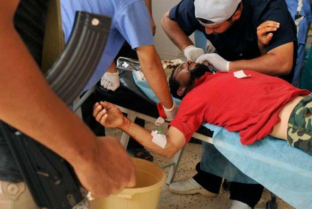 Un rebelde libio es atendido en un hospital de campana fuera de Sirte (Bela Szandelszky/AP).