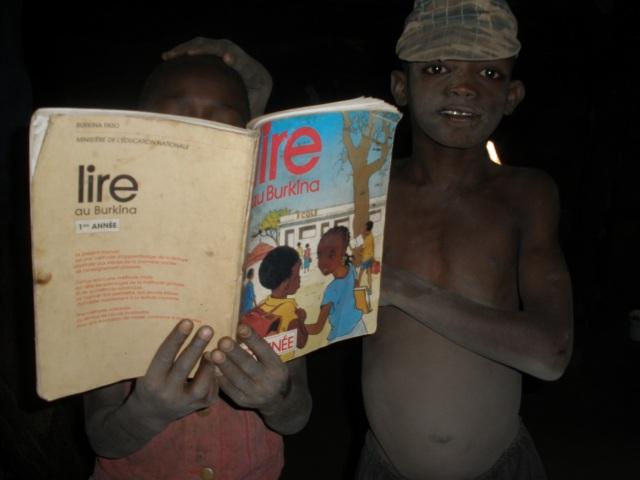 Dos niños con un libro de educación básica de Brukina Faso (Foto: David Murcia).